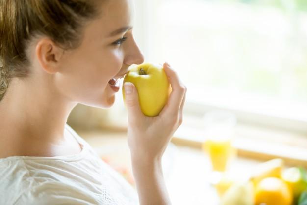 Mujer comiendo manzana para limpiar sus dientes